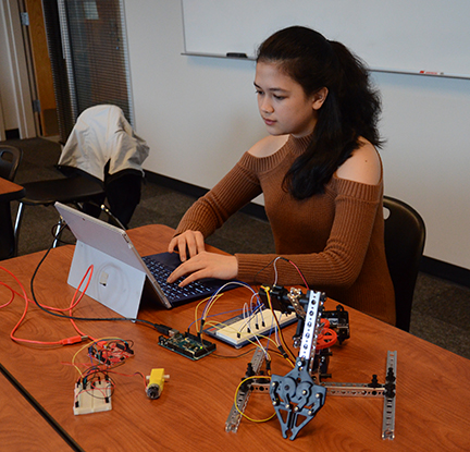 WCC engineering student works on a small robot