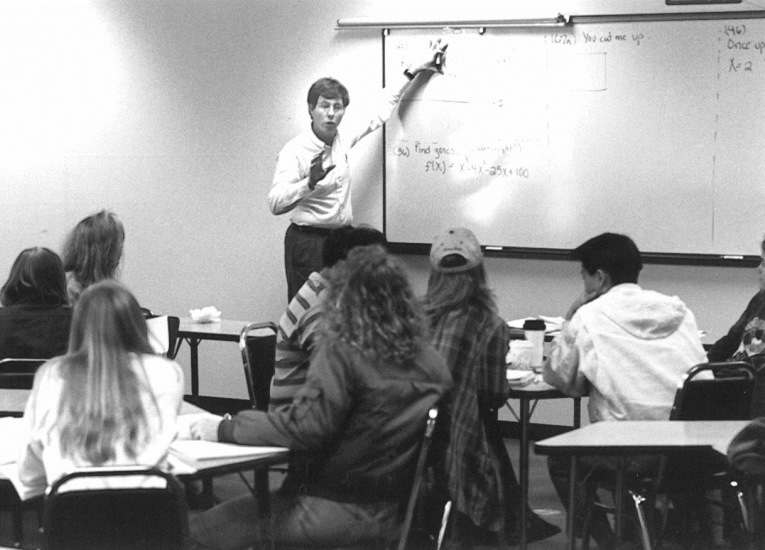 Math instructor Doug Mooers in front of class, 1990s