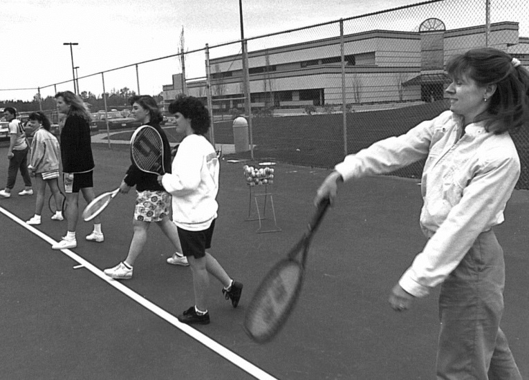 Students playing tennis on campus with Laidlaw Center in background