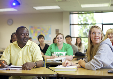 Students in class smiling and looking at board