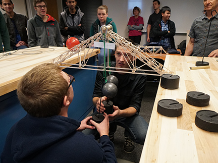 WCC engineering students hang weights on a bridge they created from popsicle sticks to test strength